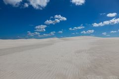 White sand and clouds against a blue sky Royalty Free Stock Photos
