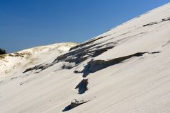 White Sand Hill. White sandy hill top with rocky ledges protruding from sand, blue sky Stock Images
