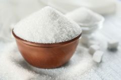 White sand and lump sugar with bowl. On wooden background royalty free stock photo