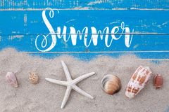 White sand star fish and shells with summer text on blue wooden Stock Image
