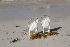 White sandals. White sandals on the beach. White sandals on the beach stock photo