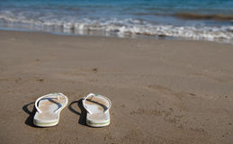 White sandals on a golden sandy beach Royalty Free Stock Photos