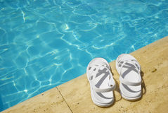 White sandals at the poolside. Sunny day and blue water Royalty Free Stock Photography