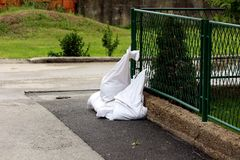 White sandbags loaded with sand left on street corner next to dark green metal fence for later use as flood protection. On rainy spring day royalty free stock photos