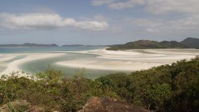 A white sandbar of a beach. A wide pan to left shot of a turquoise beach. Green plants are in the foreground stock video footage