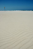 White sandy beach. Scenic view of ripples on white sandy beach with sea and blue sky background Stock Images