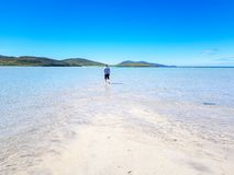 Man walking in clear blue water royalty free stock image