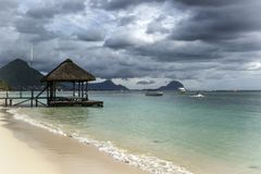 A white sandy beach with a wooden pier, boats and mountains. On Mauritius Island Royalty Free Stock Photography