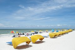 White sandy beach and yellow beach tents and umbrellas, people in the distance stock image