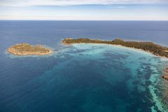 White sandy Sardinian beach with emerald waters. Aerial view. One of the many Sardinian paradise-like secluded beach. With its vivid emerald and blue hues, this stock images