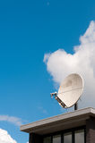 A white satellite dish on a roof. A white satellite dish on a office roof Royalty Free Stock Photo