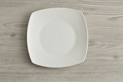 White saucer. Isolated on a wooden background Stock Photos