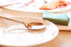 White saucer with a metal teaspoon Stock Photos