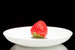 White saucer with red strawberry Stock Image