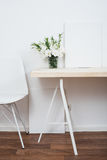 White scandinavian interior decor closeup. Empty walls, designer chair, table and natural flowers royalty free stock photos