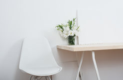 White scandinavian interior decor closeup. Empty walls, designer chair, table and natural flowers stock image