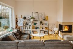 White Scandinavian living room interior with fireplace, posters, corner couch and kids toys stock image