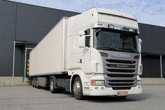 White Scania R440 Semi Truck by a Warehouse Stock Photo