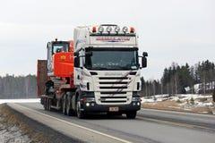 White Scania Truck Hauls Hitachi Zaxis Medium Excavator Stock Image
