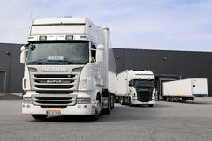 White Scania Trucks Ready to Unload at Warehouse Building. TURKU, FINLAND -  APRIL 26, 2014: White Scania trucks ready to unload at a warehouse. According to Royalty Free Stock Photography