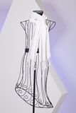 White scarf woven with fringes on mannequin. White knit scarf with fringe hanging on mannequin Royalty Free Stock Photo