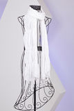 White scarf woven with fringes on mannequin. White knit scarf with fringe hanging on mannequin Stock Images