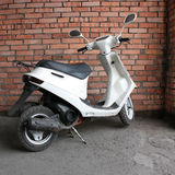 White scooter in corner wall Stock Image