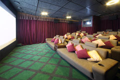 White screen and couches and projector in movie theater. White screen and couches with cushions and projector in small movie theater Royalty Free Stock Photo