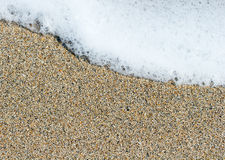 White sea foam on a yellow brown sand grains Stock Photo