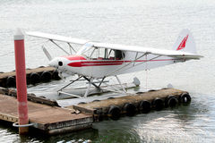 White sea plane moored at the dock. A red and white sea plane parked at a dock Stock Photography