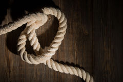 White sea rope on the wooden floor. Royalty Free Stock Photo
