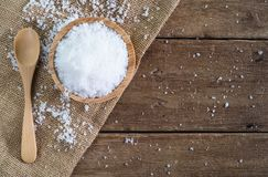 White sea salt in wood bowl with wood spoon on gunny sack cloth on brown wooden table. Top view with copy space Royalty Free Stock Photo