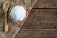 White sea salt in wood bowl with wood spoon on gunny sack cloth on brown wooden table. Top view with copy space Stock Photo