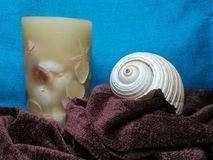 White sea shell and candle on folded scarf. White sea shell and candle on brown folded scarf, blue background Royalty Free Stock Images