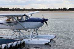 White seaplane docked at sea side jetty. Seaplane used for tourist flights docked at wharf with beach in background Royalty Free Stock Images
