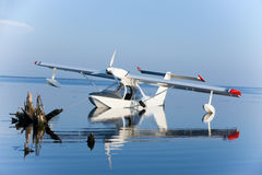 White seaplane reflection and blue lake. Airplane parked on blue water Royalty Free Stock Photo