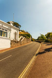 White seaside building on a hill, along an asphalt road, exotic. Plant, sunny day Stock Photography
