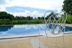 White seat next to swimming pool Royalty Free Stock Image