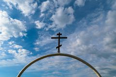 White semi-circular arch of iron pipe with dark Orthodox cross on it against the blue sky with clouds Royalty Free Stock Photo