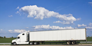 White Semi-truck. Against green field and cloudy sky Royalty Free Stock Photography