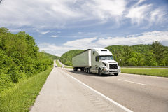 White Semi Truck On Highway In Springtime. A white semi-truck driving down the highway on a beautiful day Stock Image