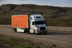 White Semi-Truck MARKINGS REMOVED. A White Semi tractor pulls an Orange trailer along a rural Wyoming interstate Stock Image