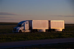 White Semi-Truck MARKINGS REMOVED. A White Semi tractor pulls a set of double white trailers along a rural Wyoming interstate Stock Image