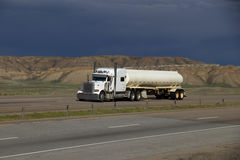 White Semi-Truck MARKINGS REMOVED. A White Semi tractor pulls a White Tanker trailer along a rural Wyoming interstate Stock Photography