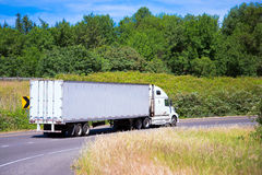 White semi truck modern trailer on turn road around green Stock Photo
