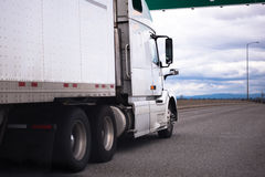 White semi-truck moving on staight highway. White modern big rig semi truck with sleeper cab and dry van trailer moving ahead wide interstate highway delivering stock photo