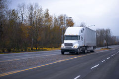 White semi truck and trailer on autumn road Royalty Free Stock Images