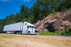 White semi truck trailer going highway with rocks green trees. White modern long haul semi truck and refrigerated trailer with a refrigeration unit moving Royalty Free Stock Photos