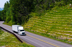 White semi truck trailer on green hill high way Royalty Free Stock Photography