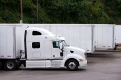 White semi truck with trailer whating cargo on parking lot in ro. A stylish modern white big rig semi truck with a large comfortable cabin and a powerful engine Royalty Free Stock Image